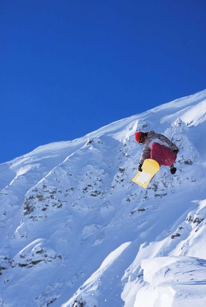 Young female snowboarder jumping off a cornice in the backcountry  Golden, British Columbia, Canada : Stock Photo