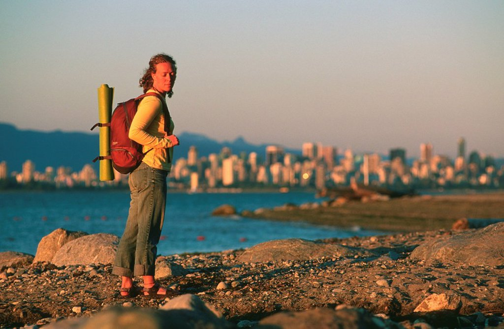 Woman walking at sunset on Jericho Beach, Vancouver, British Columbia, Canada : Stock Photo