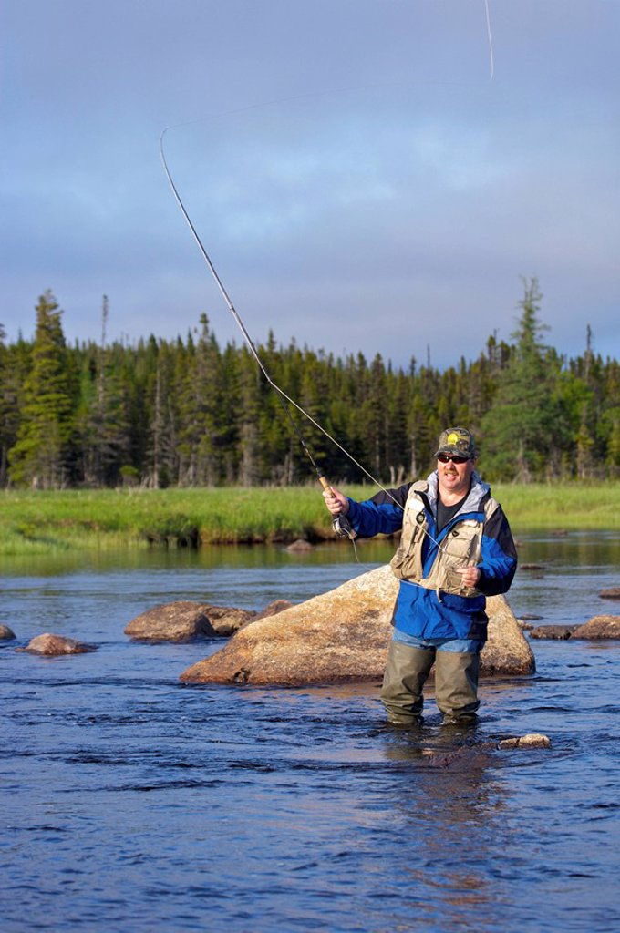 Man fly fishing in Salmon River near the town of Main Brook, Viking Trail, Great Northern Peninsula, Newfoundland & Labrador : Stock Photo