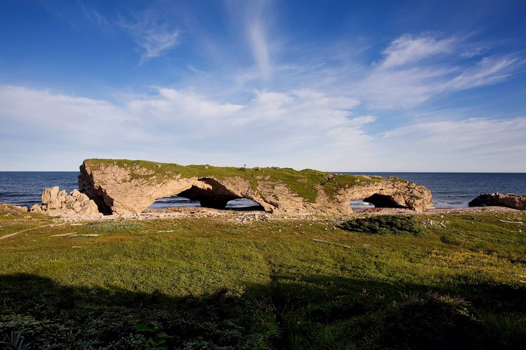 Natural rock archway created by tidal action in The Arches Provincial Park on the island of Newfoundland, Newfoundland and Labrador, Canada : Stock Photo