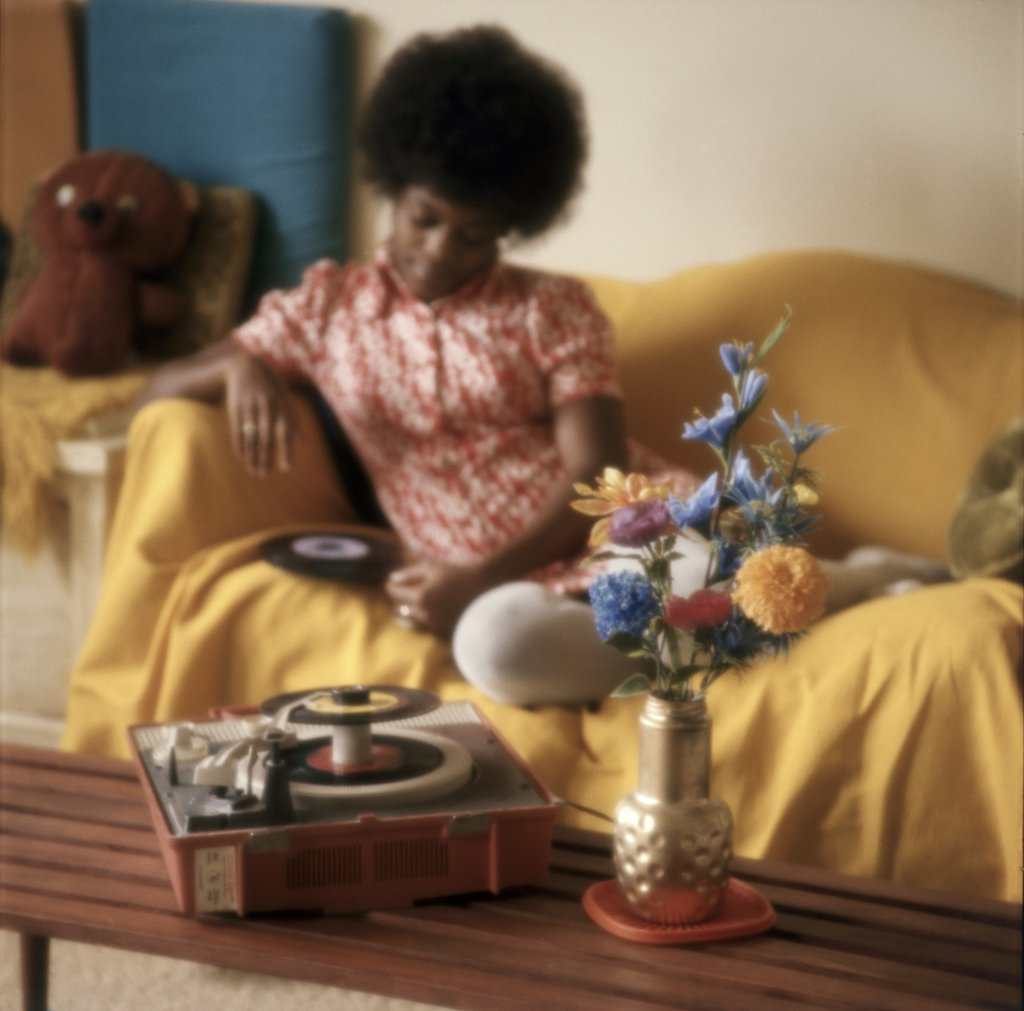 Young woman reclining on a couch and looking at a record : Stock Photo
