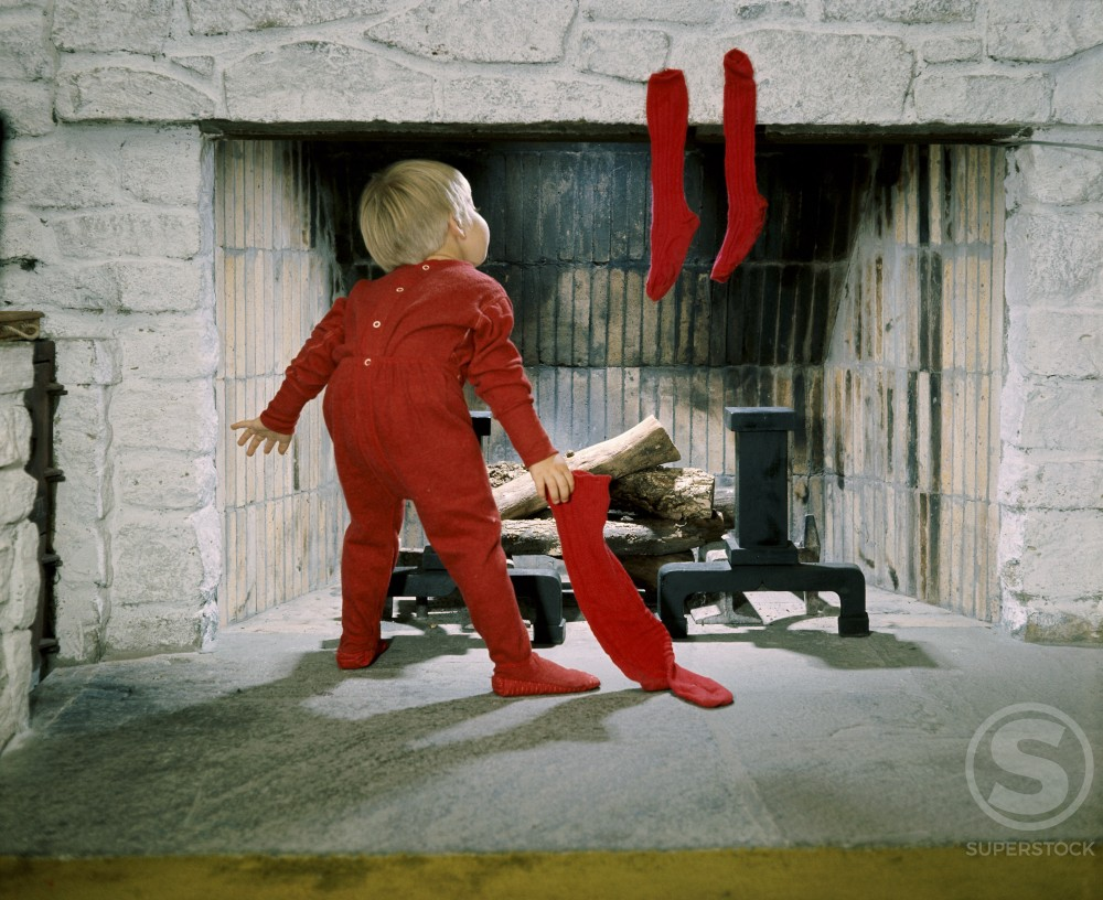 Rear view of a boy holding stockings near a fireplace : Stock Photo