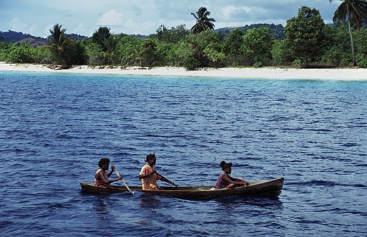 Three people rowing a boat in the ocean, Solomon Islands : Stock Photo