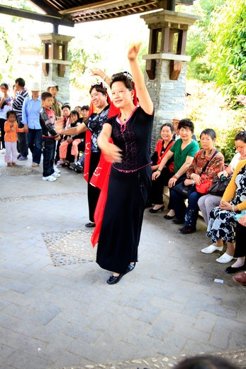 China, Kunming, Women dancing in front of audience : Stock Photo