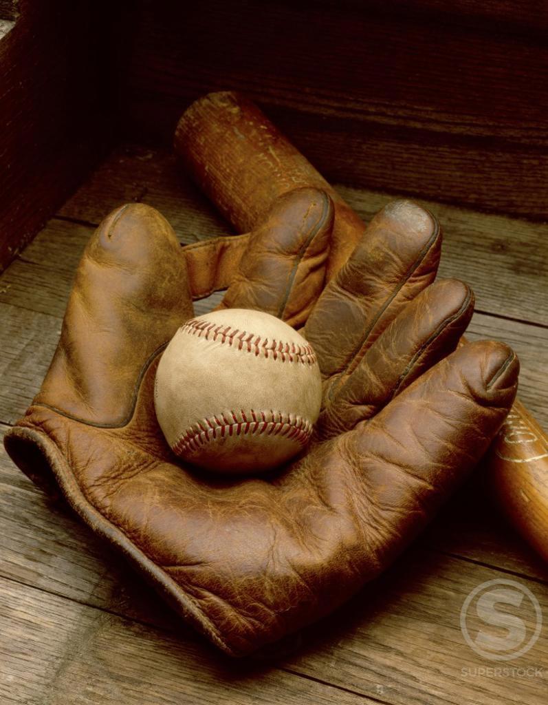 Stock Photo: 204-957A Close-up of a baseball glove with a baseball bat and a baseball