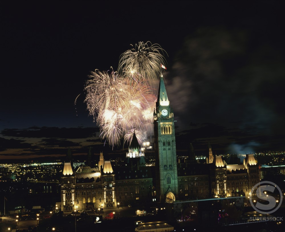 Fireworks over a city, Canada Day, Parliament Hill, Ottawa, Canada : Stock Photo