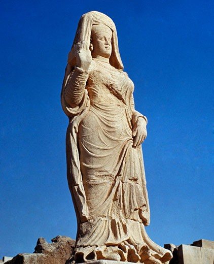 Iraq, Hatra, female stone sculpture against blue sky : Stock Photo