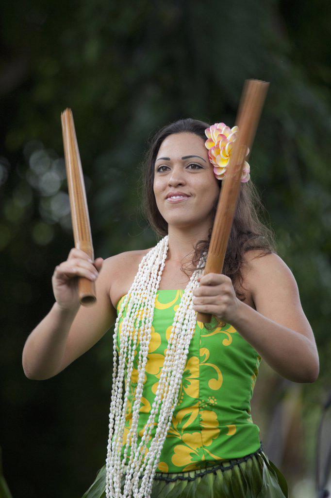 Hawaii, Kona, Traditional kahiko hula dancer with pu'ili (bamboo rattle sticks) at hula performance : Stock Photo