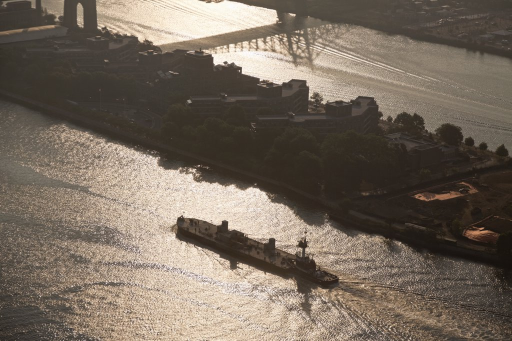 Stock Photo: 2117-588528B USA, New York City, Aerial view of tugboat pushing barge up East River