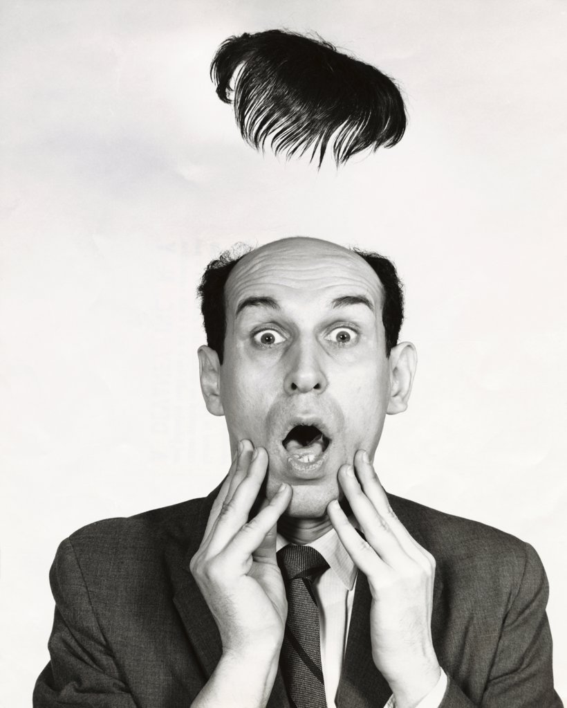 Toupe flying off of a surprised businessman's head : Stock Photo