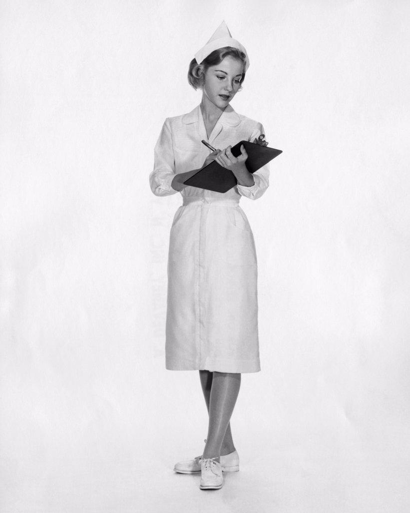 Stock Photo: 255-11709 Female nurse writing on a clipboard