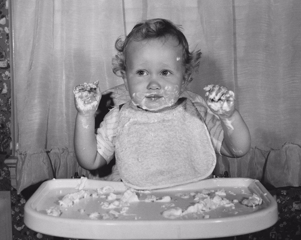 Stock Photo: 255-1176A Close-up of a baby sitting in a high chair with food on his face and hands