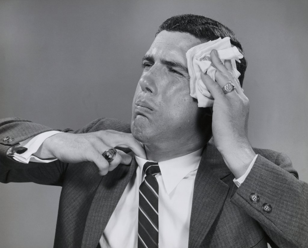 Close-up of a businessman wiping his face with a handkerchief : Stock Photo