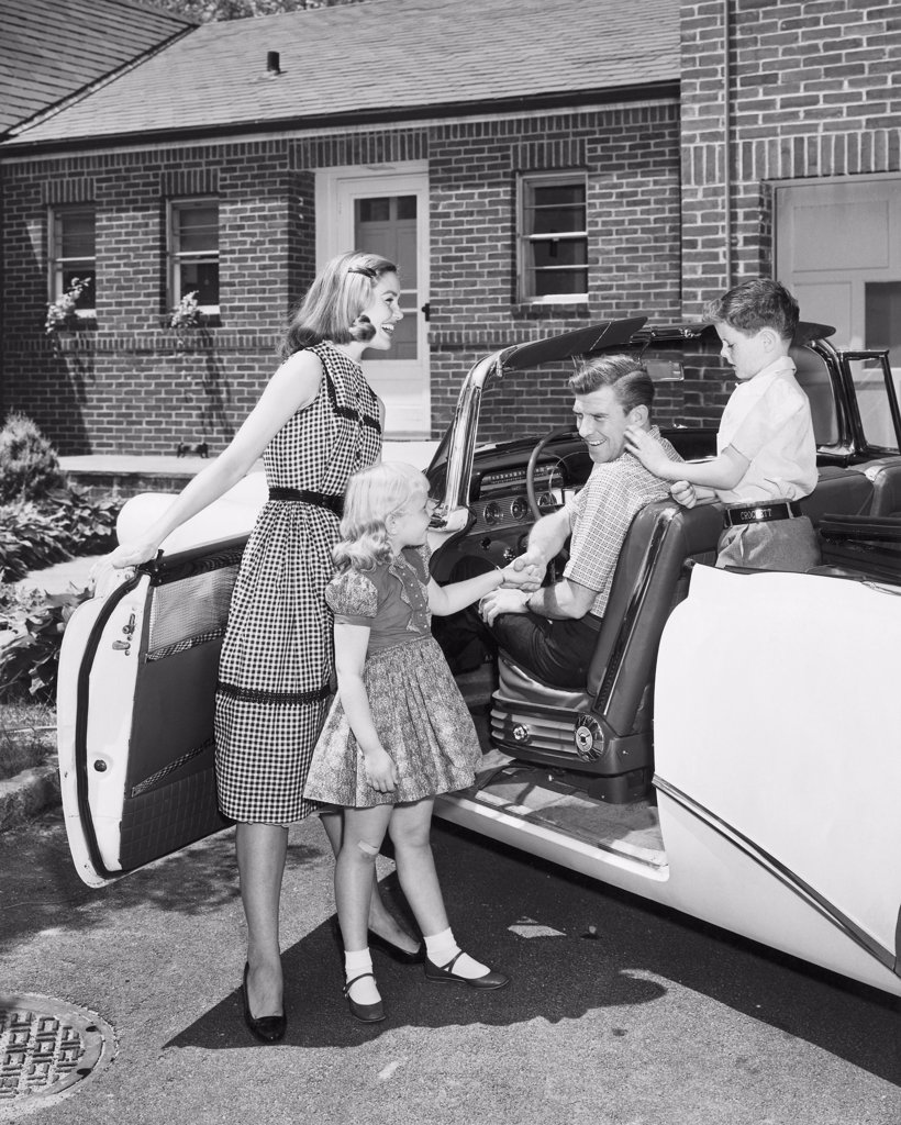 Stock Photo: 255-11950 Mid adult woman and her daughter standing beside a car with a mid adult man and his son sitting in a car