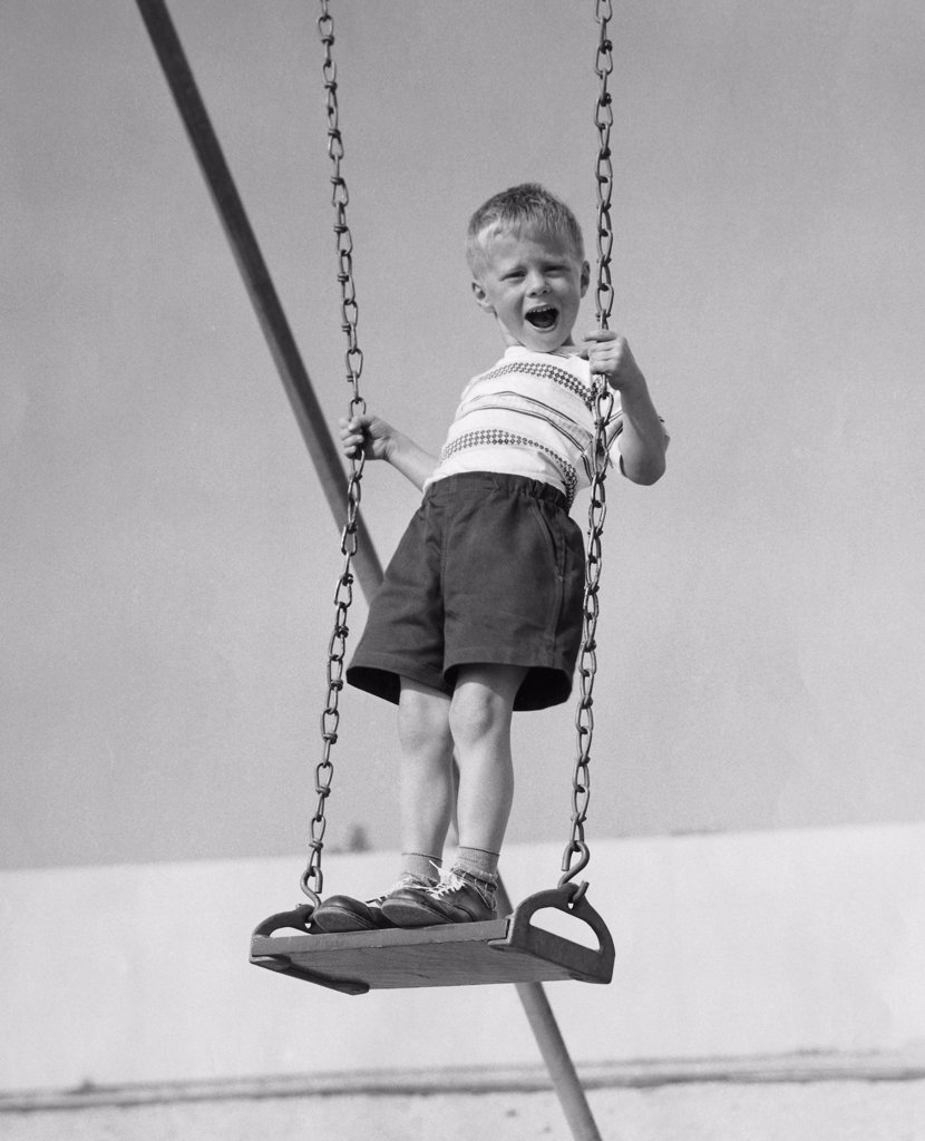 Stock Photo: 255-12885C Boy standing on a swing and screaming