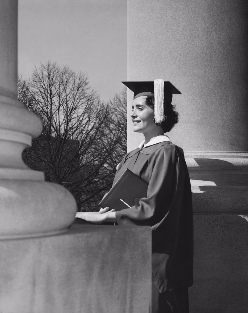Stock Photo: 255-15034 Side profile of a young woman dressed in a graduation gown, smiling