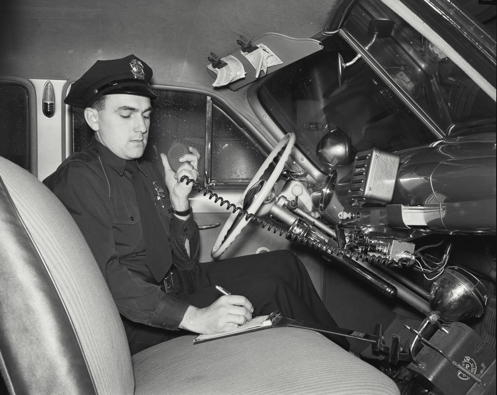Police officer sitting in a police car and talking on a CB radio : Stock Photo