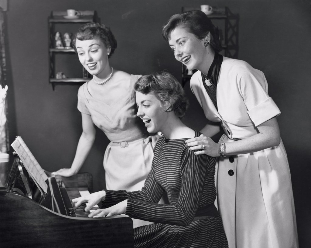 Side profile of a young woman playing the piano with two young women standing behind her : Stock Photo