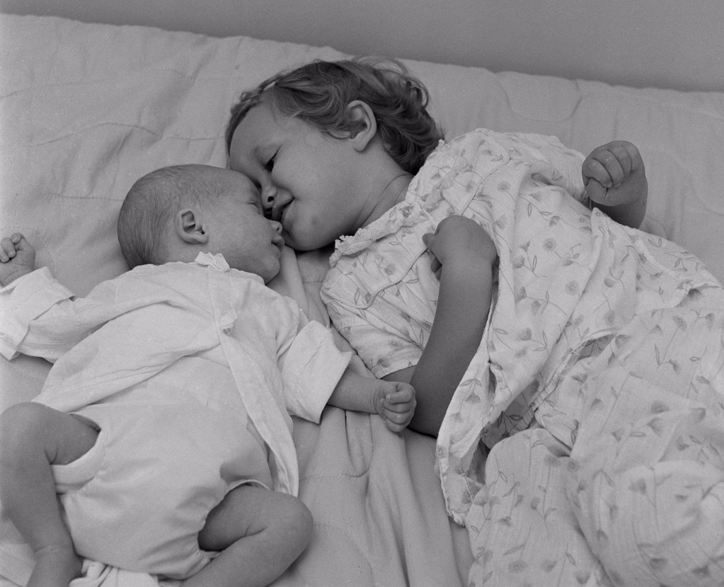 Baby lying with sister on bed : Stock Photo