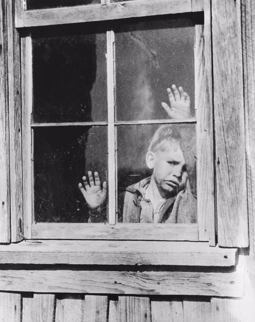 Boy looking through a window : Stock Photo