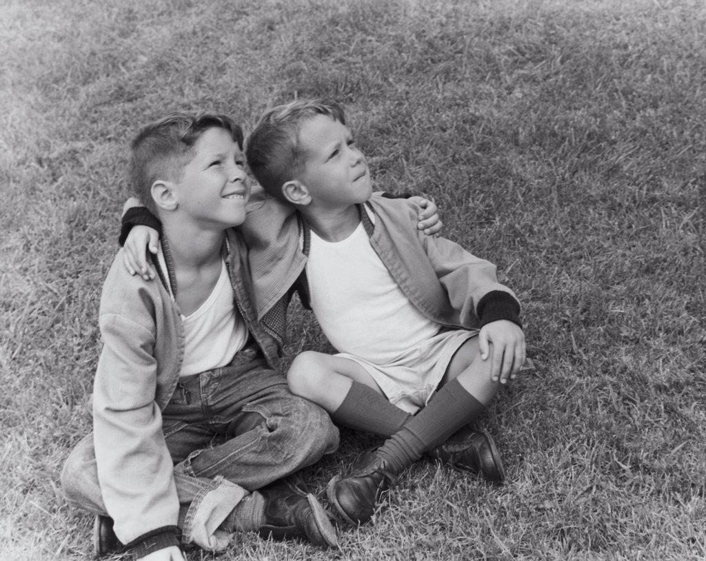 Stock Photo: 255-16249 Two boys sitting on the grass with their arms around each other