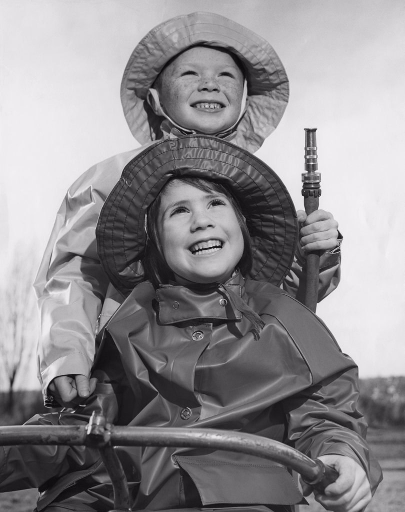 Close-up of a girl and her brother wearing raincoats and smiling : Stock Photo