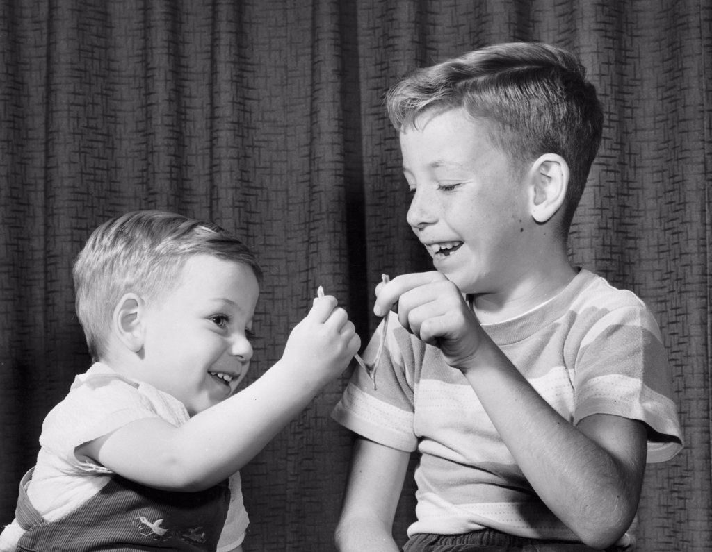 Stock Photo: 255-16519A Two boys pulling a wishbone and smiling