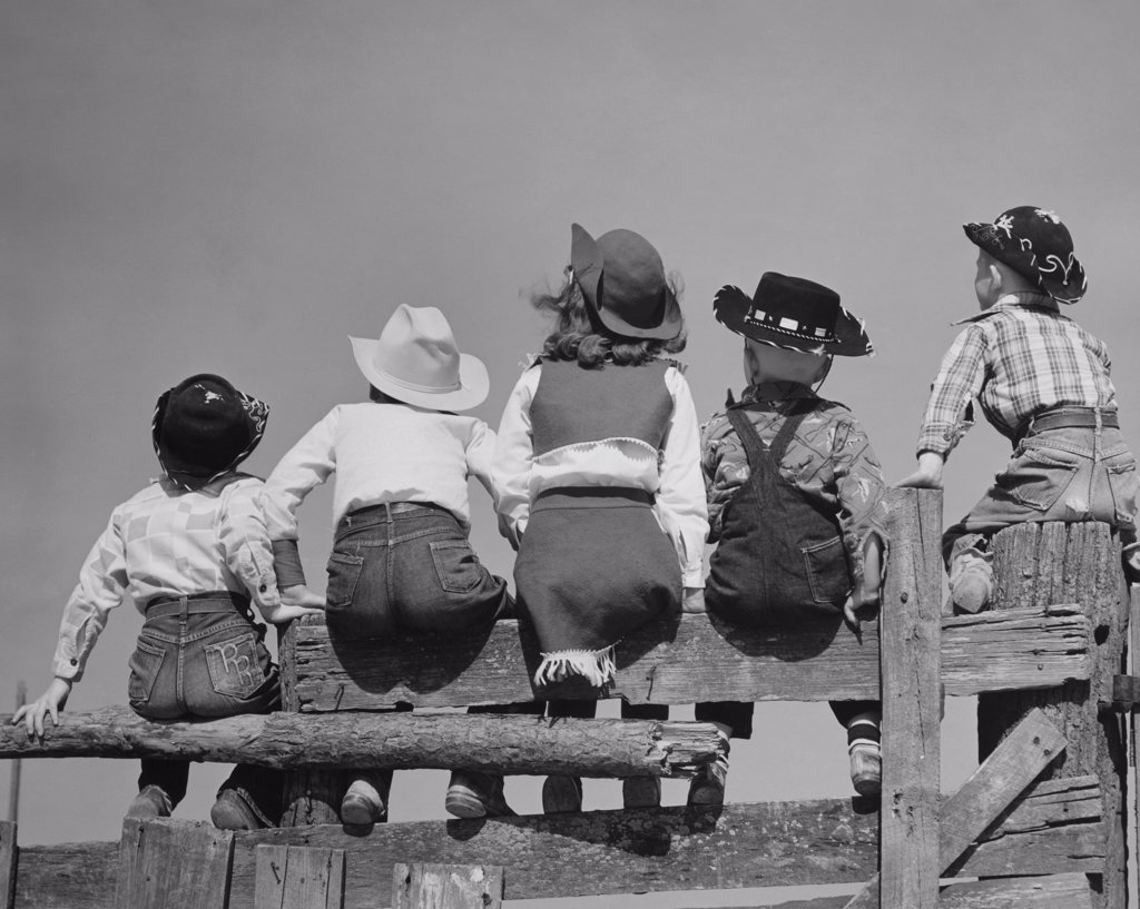 Rear view of five children sitting on a wooden fence : Stock Photo