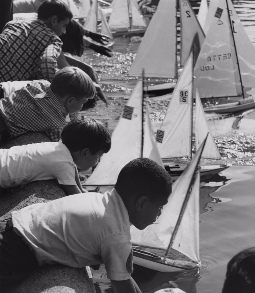 Stock Photo: 255-16576 Group of children placing their toy boats in water for a race