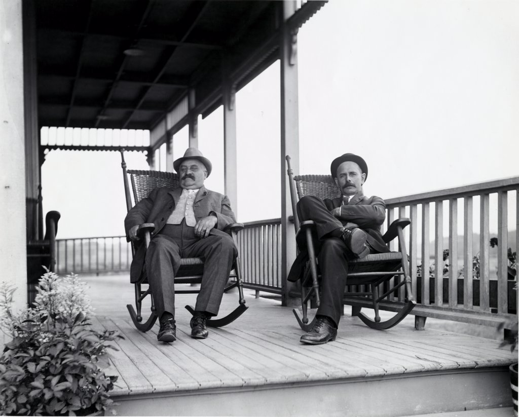 Portrait of two mature men sitting on rocking chairs : Stock Photo