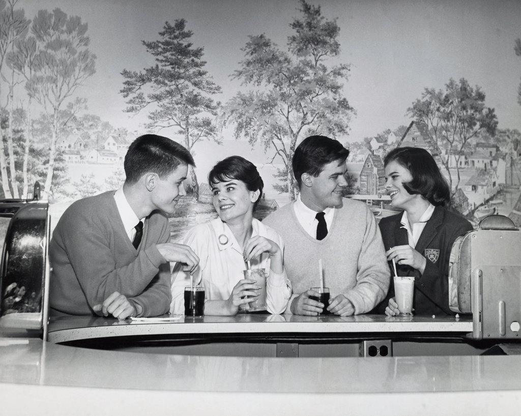 Two teenage couples sitting in a restaurant and smiling, 1960 : Stock Photo