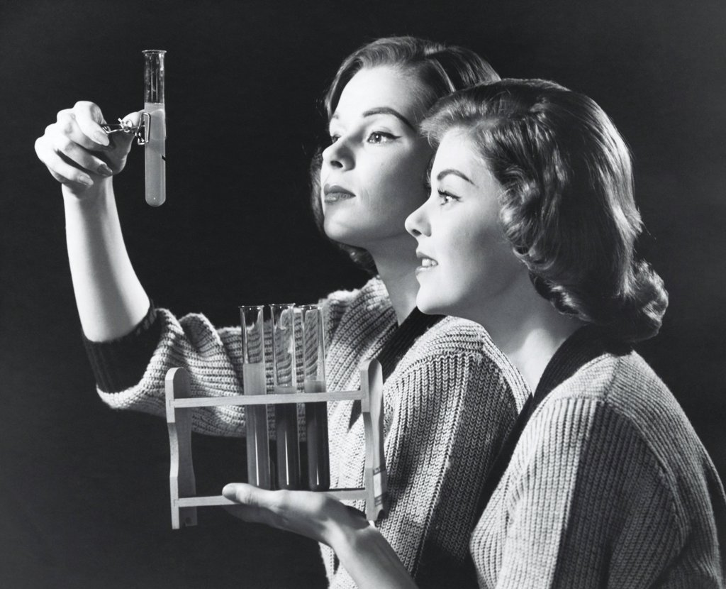 Two young women examining a solution in a test tube : Stock Photo