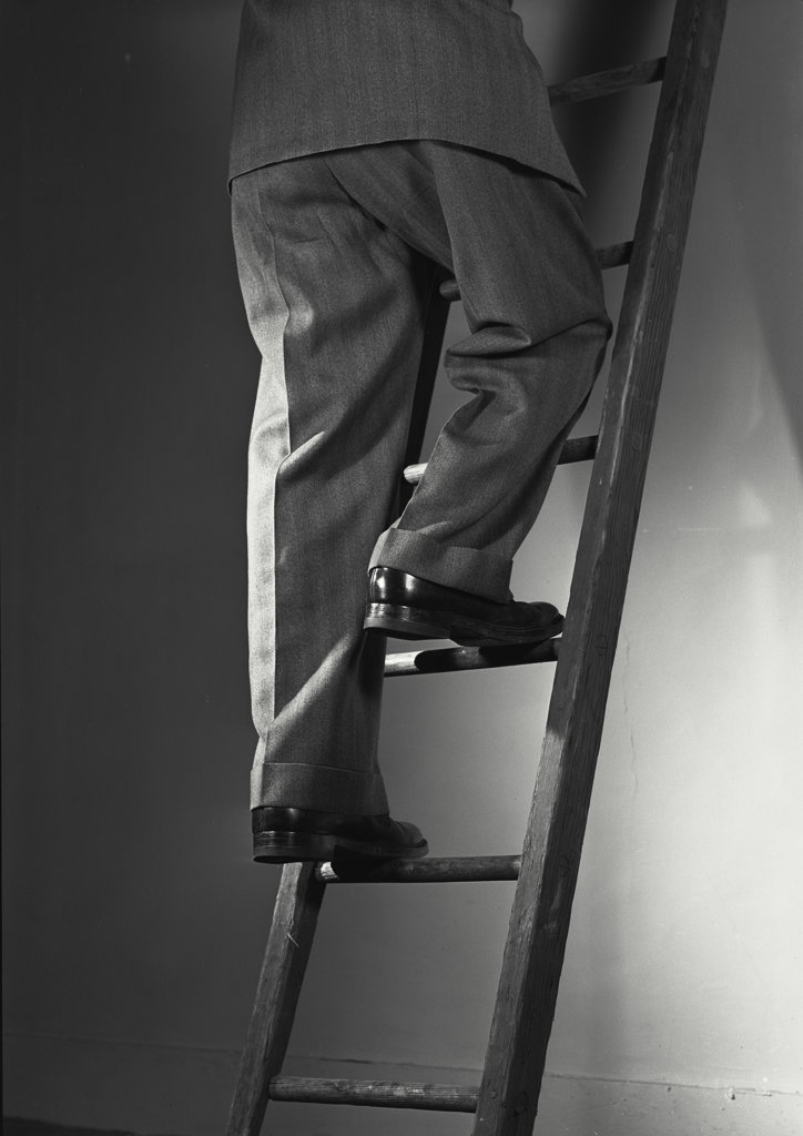 Stock Photo: 255-18714 Low section view of a businessman climbing up a ladder