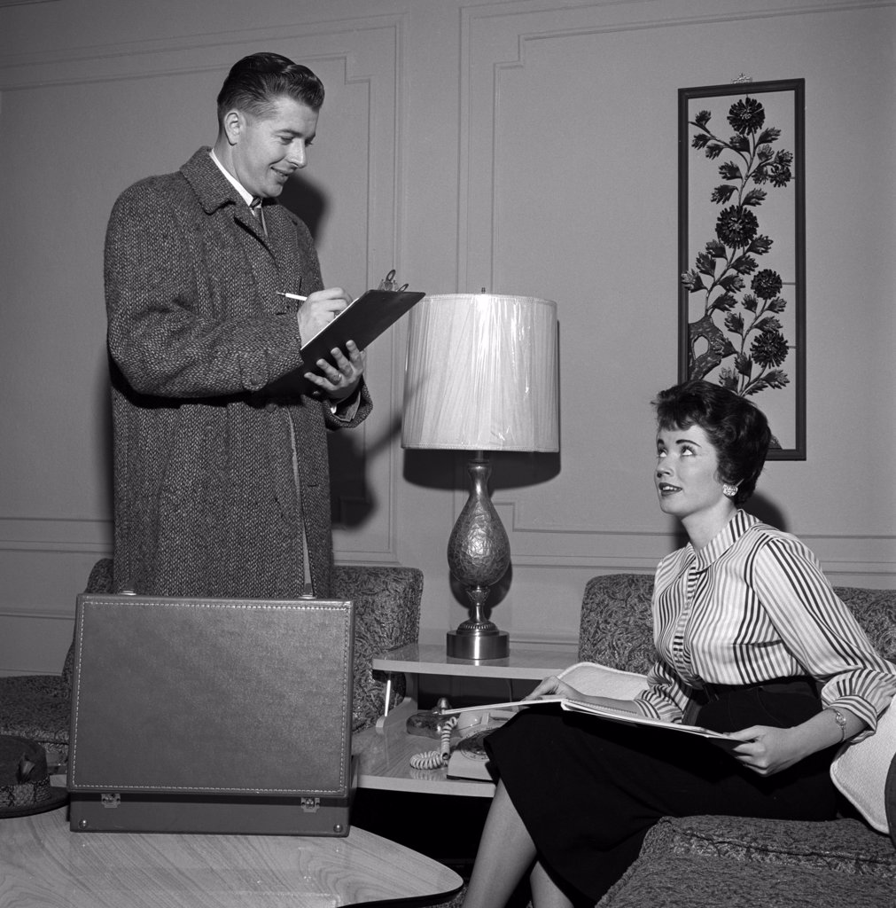 Stock Photo: 255-18737 Insurance agent filling in form, while young woman is sitting on sofa holding open brochure