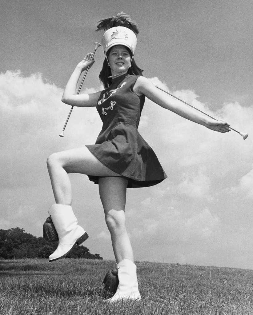 Low angle view of a drum majorette performing with two twirling batons in a field : Stock Photo