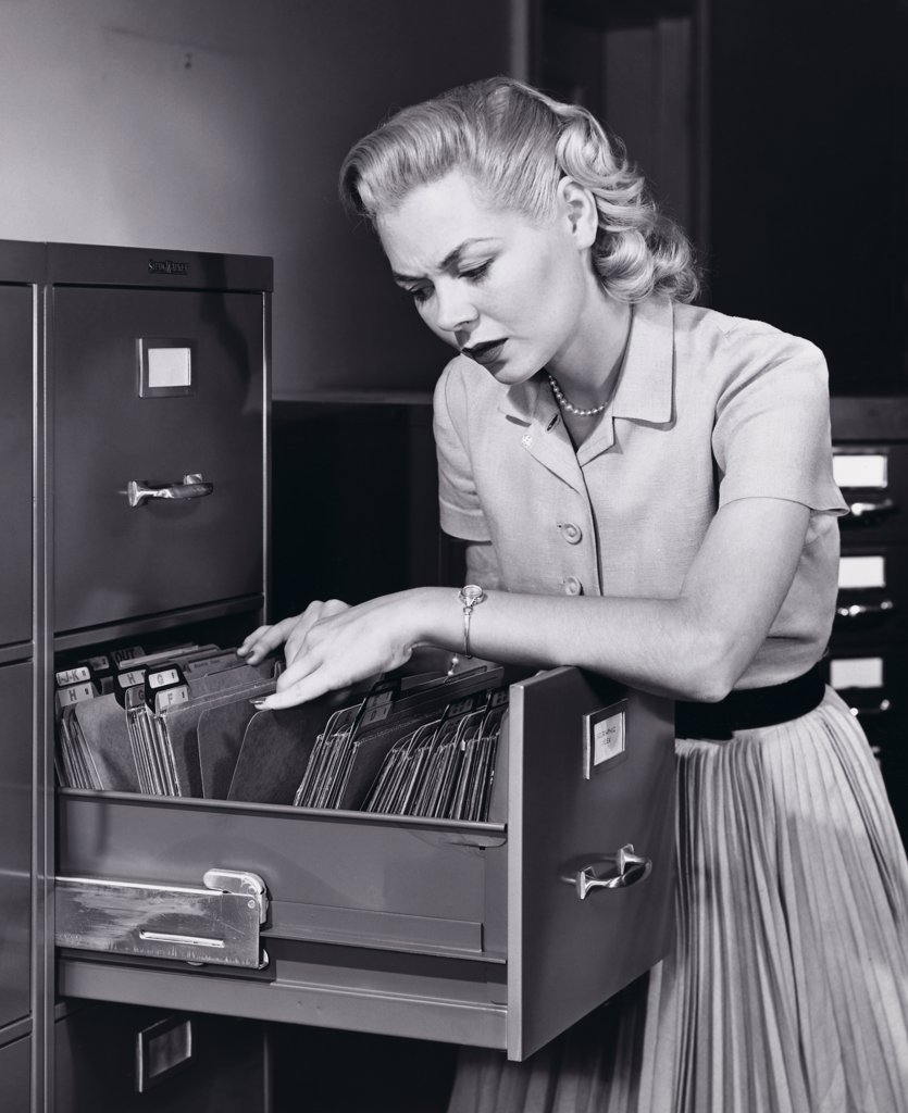 Businesswoman searching for files in a filing cabinet : Stock Photo
