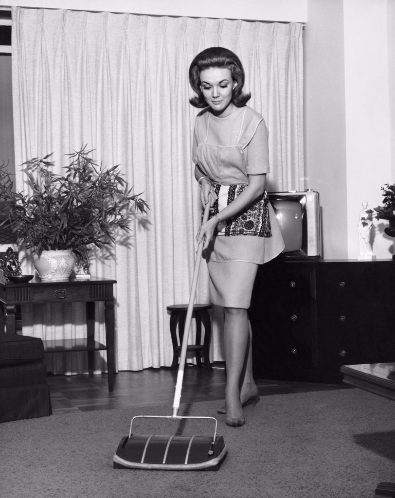 Young woman cleaning carpet : Stock Photo