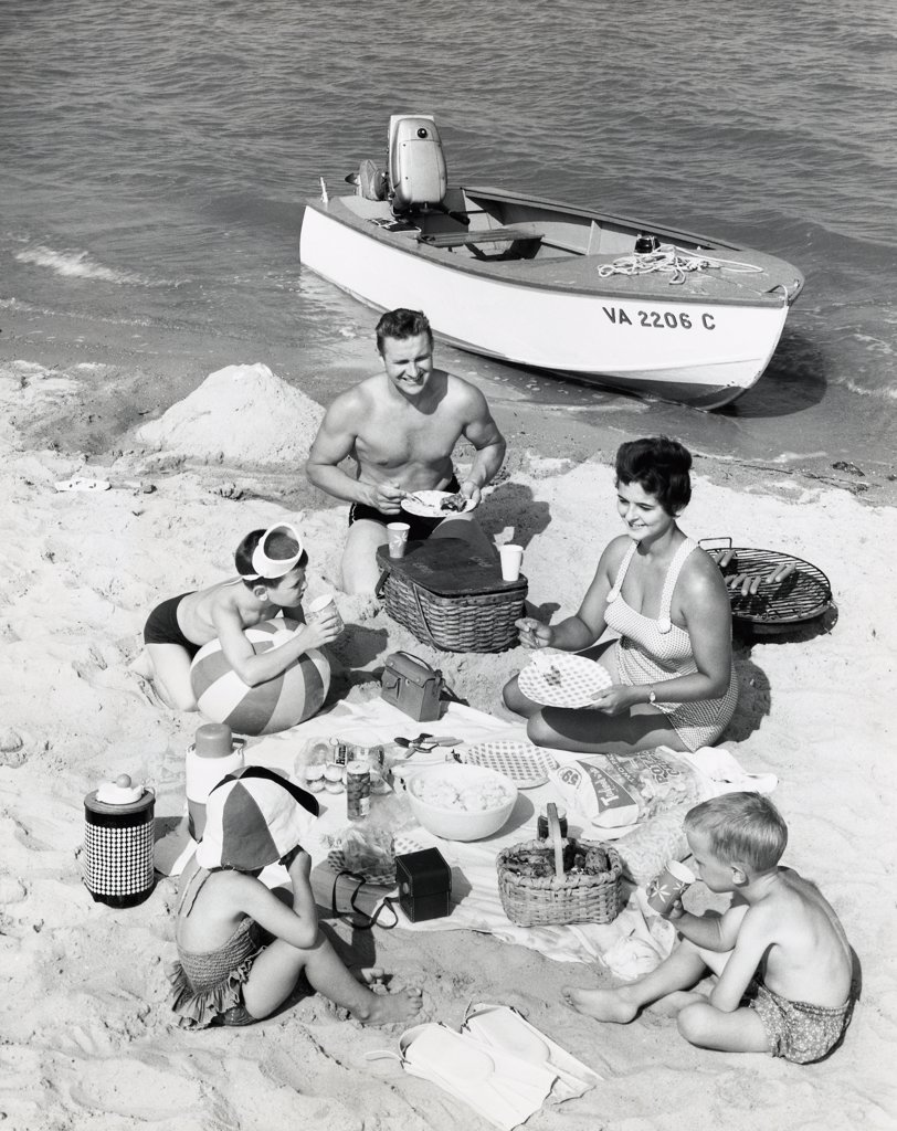 Parents with three children having picnic on beach : Stock Photo