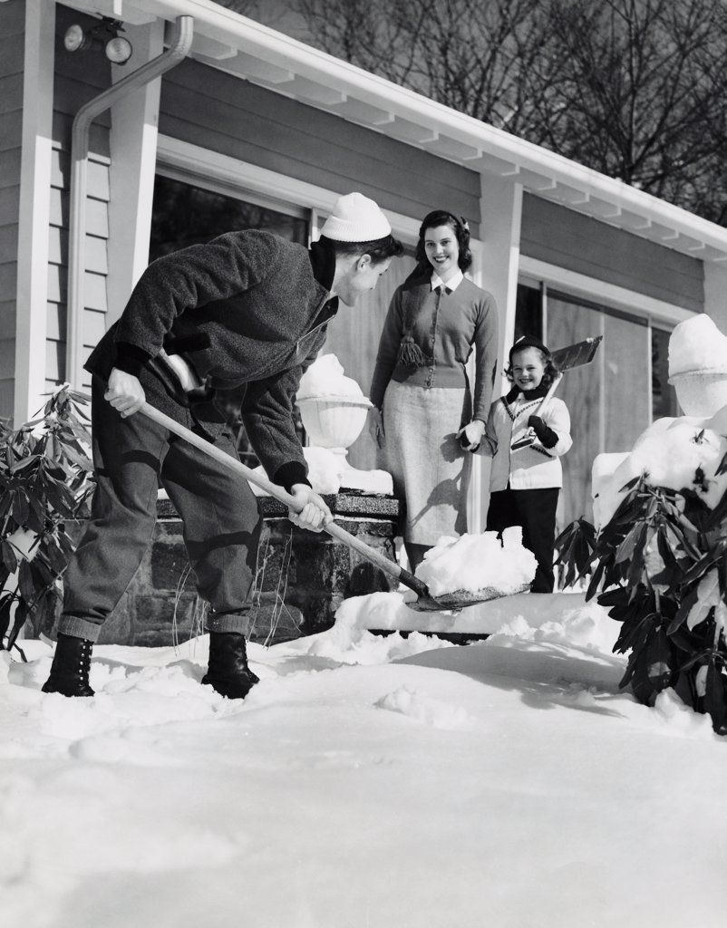 Father removing snow from the front yard of his house and his wife and daughter watching him : Stock Photo