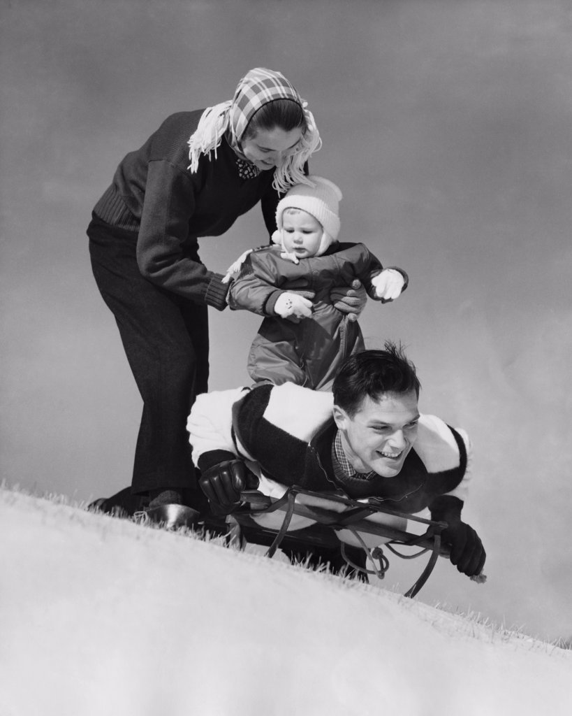 Stock Photo: 255-20113 Low angle view of parents and their son on a sled
