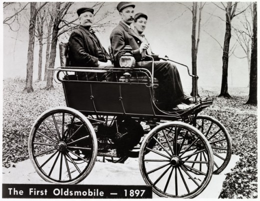 Two young men with a mature man sitting in an Oldsmobile, 1897 : Stock Photo