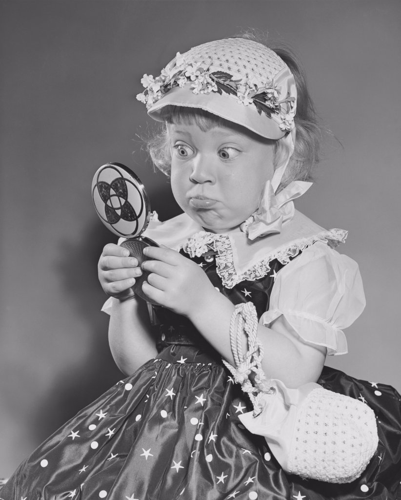 Close-up of a girl holding a hand mirror and making a face : Stock Photo