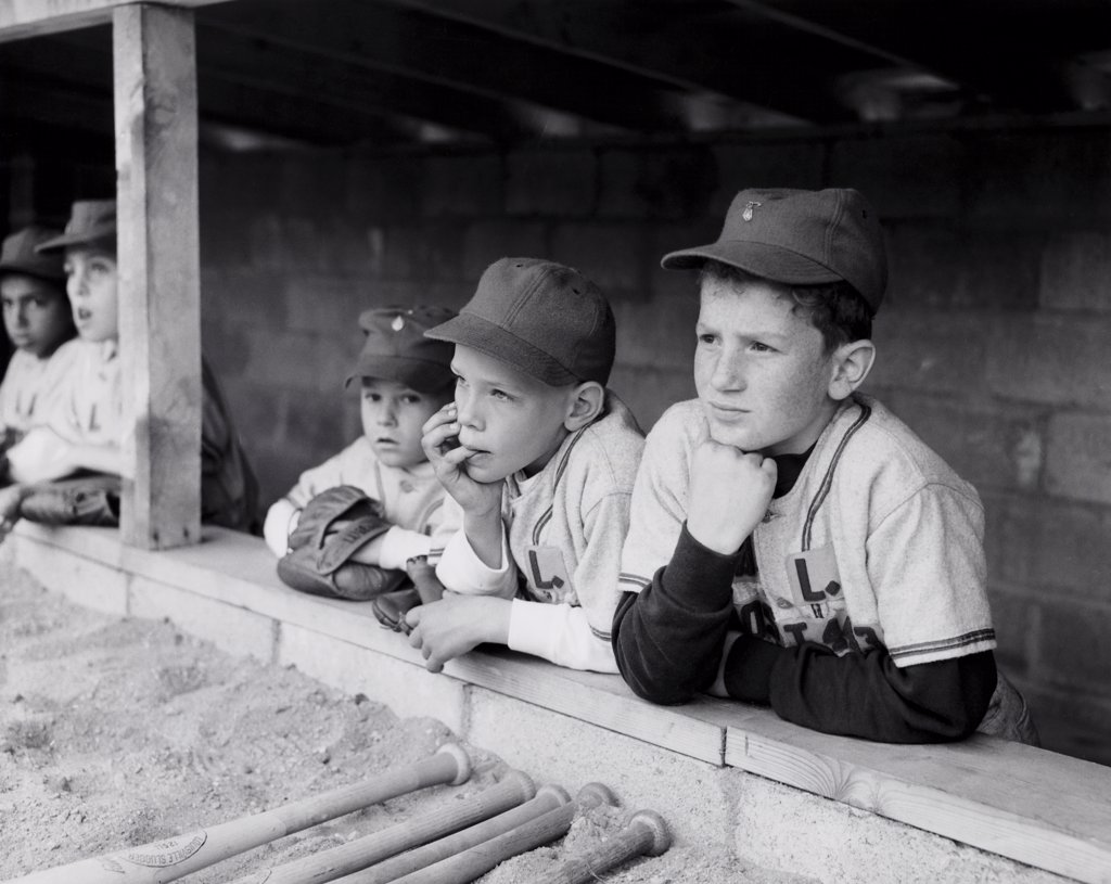 Youth league baseball players standing in a dugout : Stock Photo