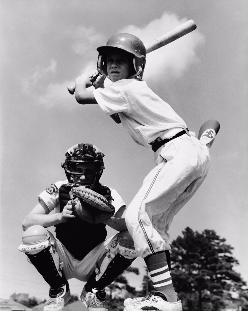 Stock Photo: 255-20445 Youth league baseball player batting with a baseball catcher squatting behind him