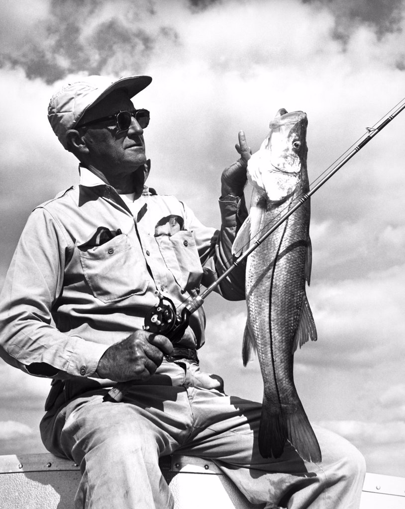 Stock Photo: 255-21059 Mid adult man holding a fish and a fishing rod