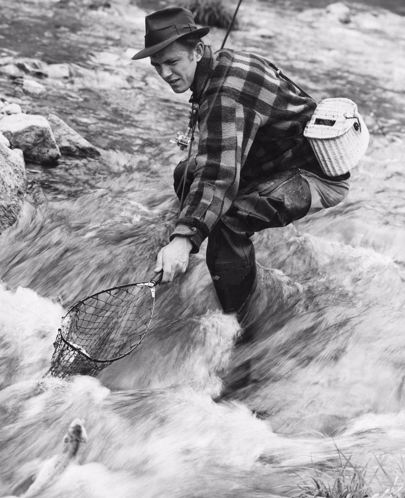 Side profile of a mid adult man fishing in a river : Stock Photo
