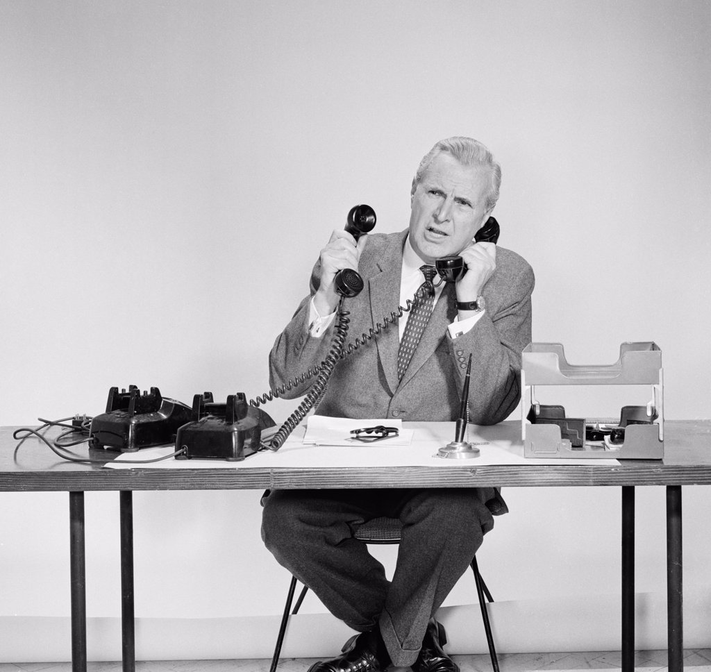 Stock Photo: 255-2192 Businessman using two telephones