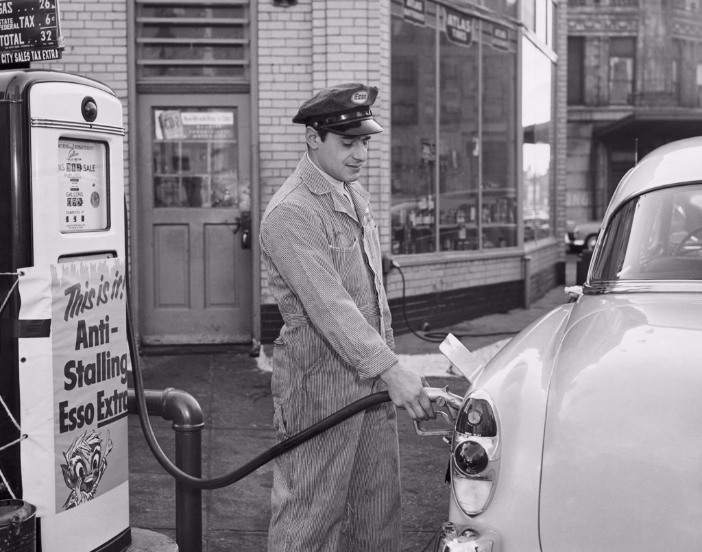 Side profile of a gas station attendant filling up a car : Stock Photo
