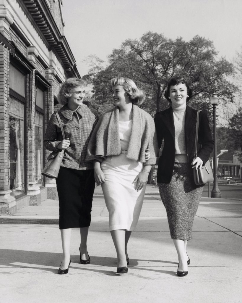 Three young women walking on the sidewalk : Stock Photo