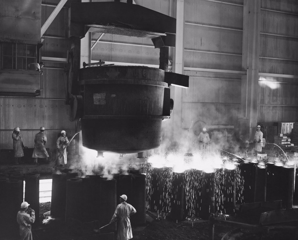Molten steel being poured into molds in a steel factory : Stock Photo